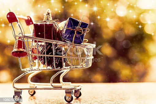 Xmas decorative items in mini shopping cart or trolley against blurred natural green background for Christmas and New Year festival concept (added glowing star and color filter effect)