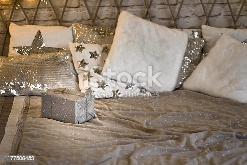 Xmas in morning bedroom. Double bed In christmas Interior on white wall background with cozy lights. Gift box on bed. Many pillows on bed.
