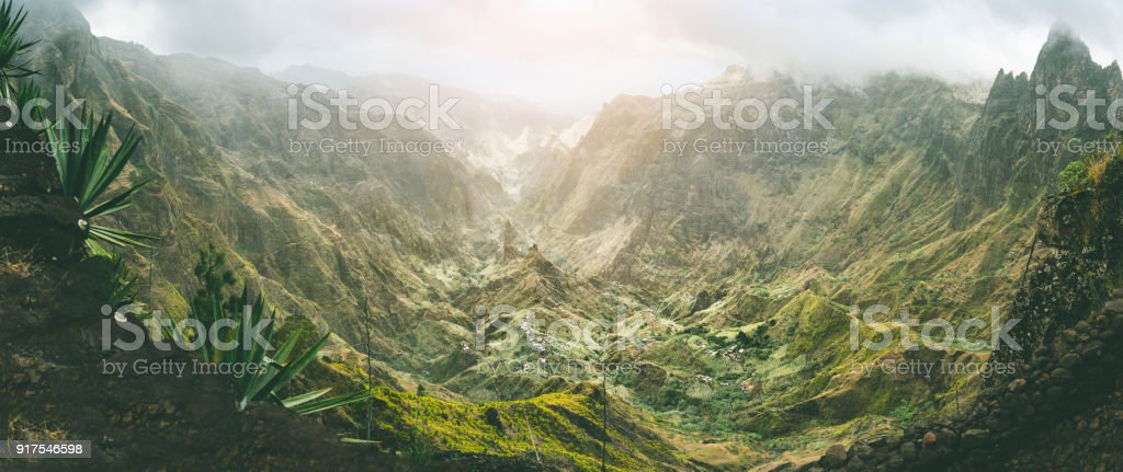 Xo-Xo valley with harsh peaks surrounded by mountains. Slopes are covered by agave plants. Small local village located in the valley. Santo Antao island, Cape Verde. Panoramic shot stock photo