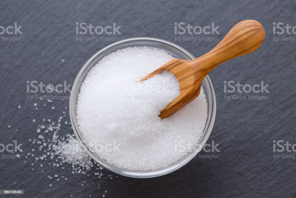 xylitol or birch sugar in a wooden scoop and glass bowl on black background, selective focus stock photo