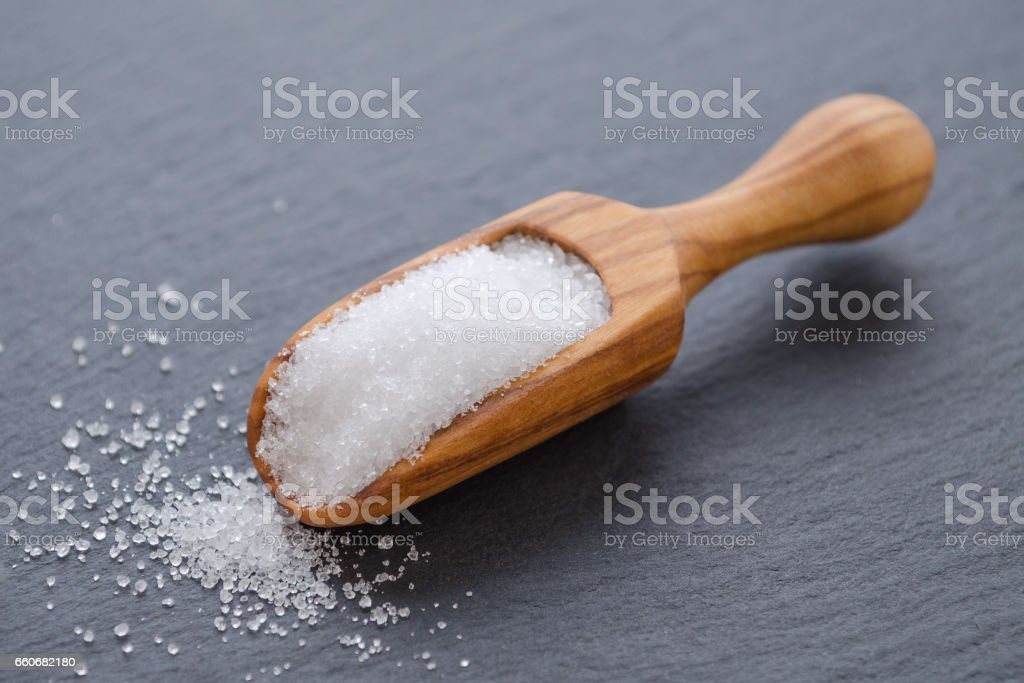 xylitol or birch sugar in a wooden scoop on black background, selective focus stock photo