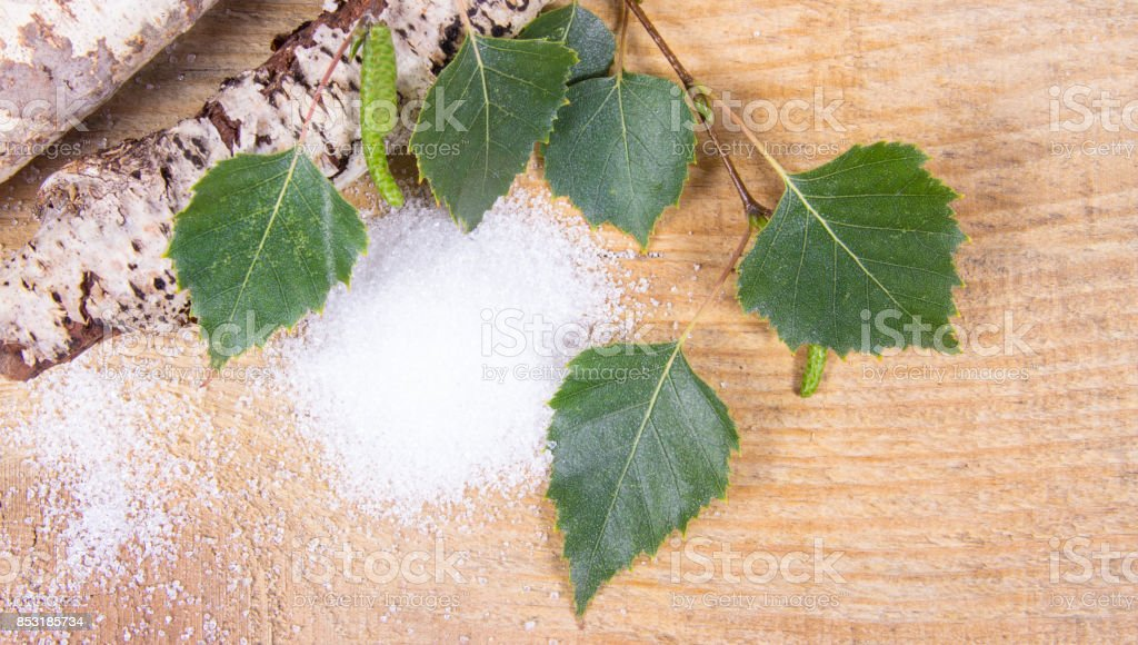 Xylitol - sugar substitute. Birch sugar on wooden background. stock photo