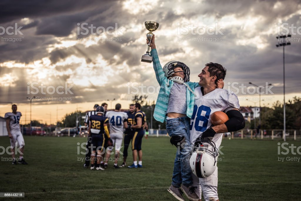 Yaaay, my daddy won a trophy in American football game! stock photo