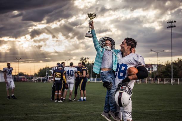 Yaaay, my daddy won a trophy in American football game! stock photo