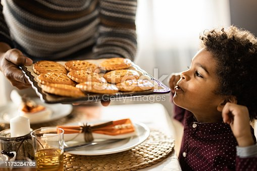 Small African American boy feeling satisfied while his unrecognizable father is bringing him baked cookies.