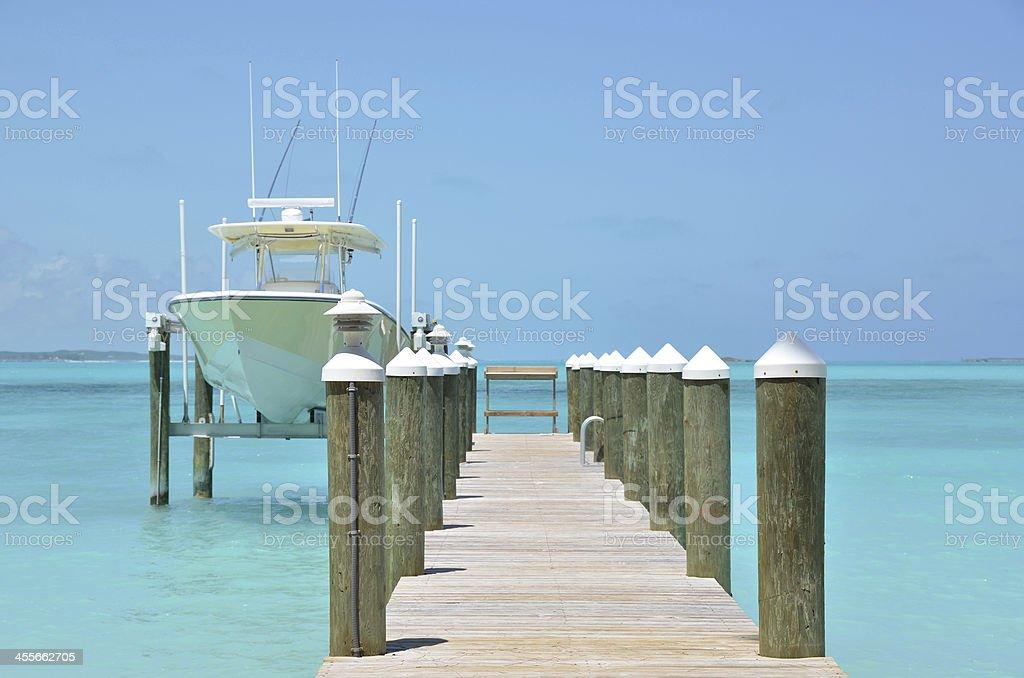 A yacht at a wooden jetty in Exuma, Bahamas royalty-free stock photo