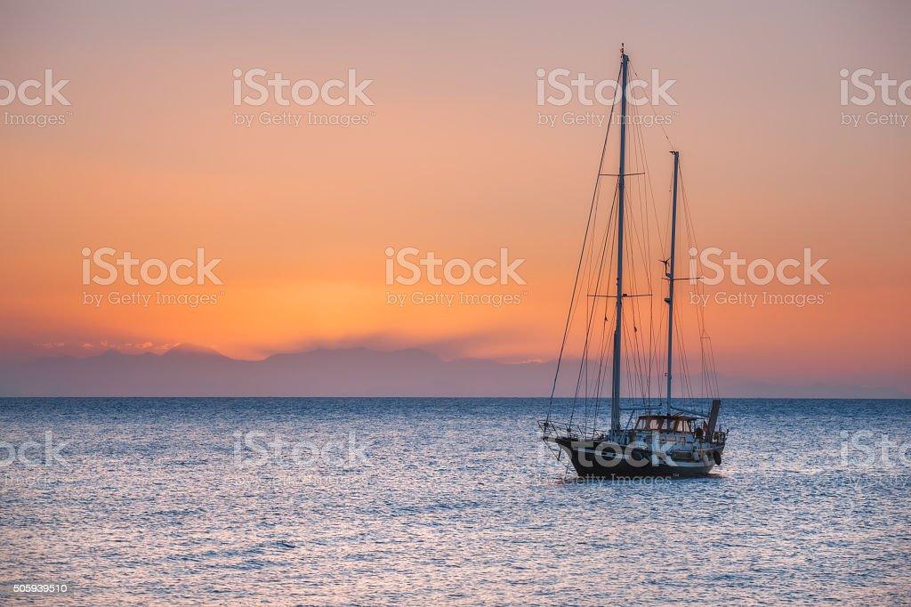 Yacht at sunrise in the Mediterranean Sea. Rhodes Island. Greece. stock photo