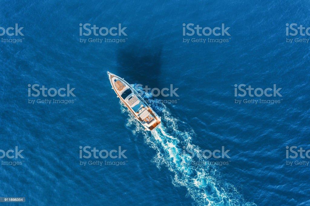 Yacht à la mer en Europe. Vue aérienne de luxe flottant bateau au coucher du soleil. Paysage coloré avec le bateau dans la baie de marina, mer bleue. Vue de dessus depuis un drone d'yacht. Croisière de luxe. Paysage marin avec le bateau à moteur photo libre de droits
