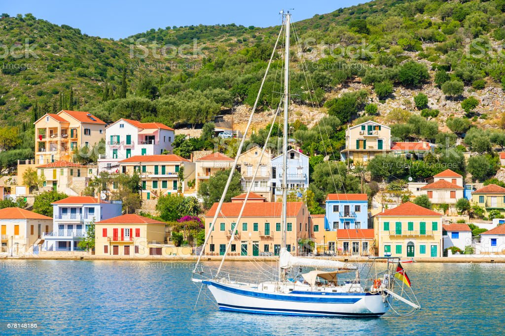 Yacht boat on sea with colourful houses of Vathi town in background, Ithaca island, Greece stock photo