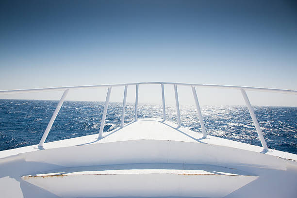 yacht cruising into open water - yacht front view stock photos and pictures