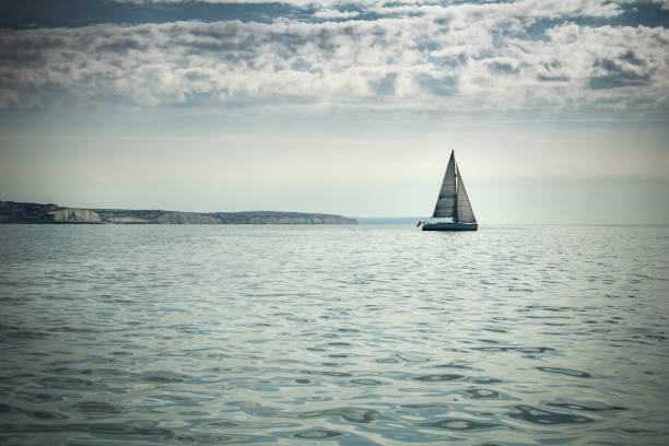 Yacht heading out to sea on Sussex coast stock photo