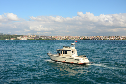 yacht in the blue sea under blue sky with white clouds in Istanbul