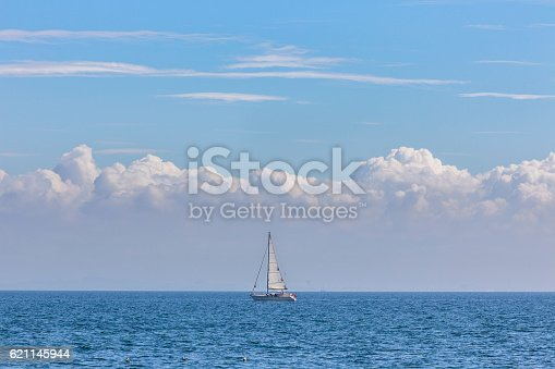 Yacht in the centre with white sails in the blue open sea