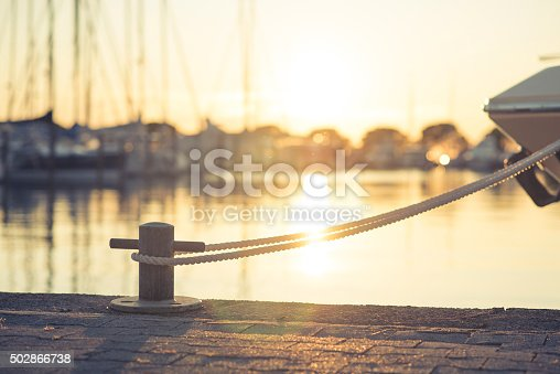 Yacht in port tied with a rope on mooring post on harbour during sunset. Sun and reflection of it in back.
