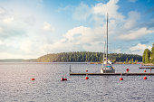 Yacht near the mini pier on Lake in Finland. On a summer evening