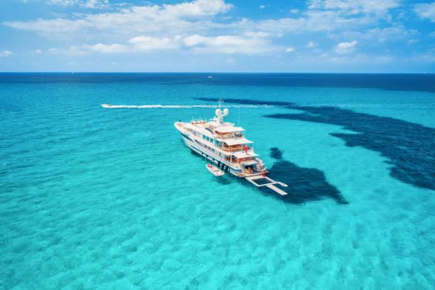 Segelyacht am azurblauen Meer in Balearen. Luftaufnahme der schwimmende Boot mit Leuten im transparenten Meer am sonnigen Tag im Sommer. Draufsicht von Drohne. Seelandschaft mit Luxus Yachten in der Bucht in Bewegung – Foto