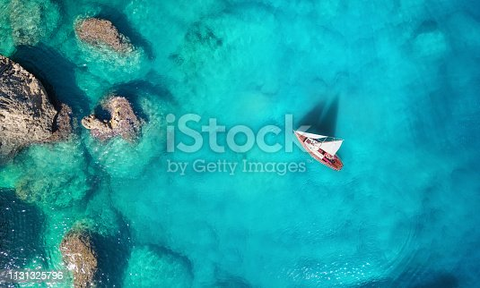 1127346848 istock photo Yacht on the sea from top view. Turquoise water background from top view. Summer seascape from air. Travel concept and idea 1131325796