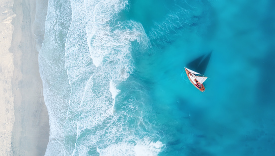 istock Yacht on the water surface from top view. Turquoise water background from top view. Summer seascape from air. Travel concept and idea 1066331604