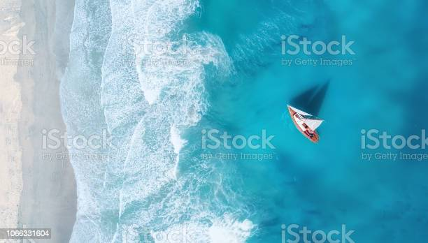Photo of Yacht on the water surface from top view. Turquoise water background from top view. Summer seascape from air. Travel concept and idea