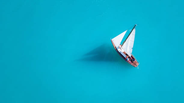 yacht on the water surface from top view. turquoise water background from top view. summer seascape from air. travel concept and idea - sail stock pictures, royalty-free photos & images