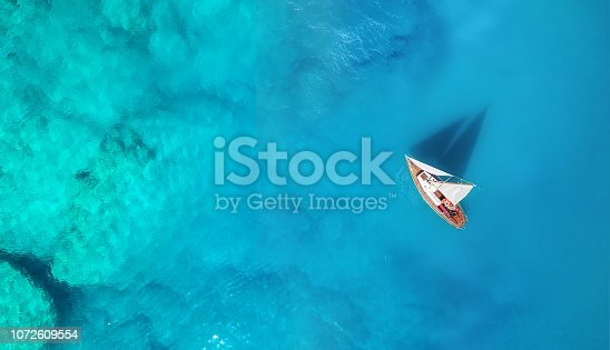 1066331604 istock photo Yacht on the water surface from top view. Turquoise water background from top view. Summer seascape from air. Travel concept and idea 1072609554