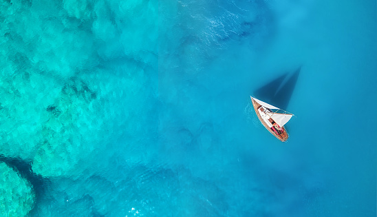 istock Yacht on the water surface from top view. Turquoise water background from top view. Summer seascape from air. Travel concept and idea 1072609554