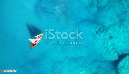 1066331604 istock photo Yacht on the water surface from top view. Turquoise water background from top view. Summer seascape from air. Travel concept and idea 1090585080