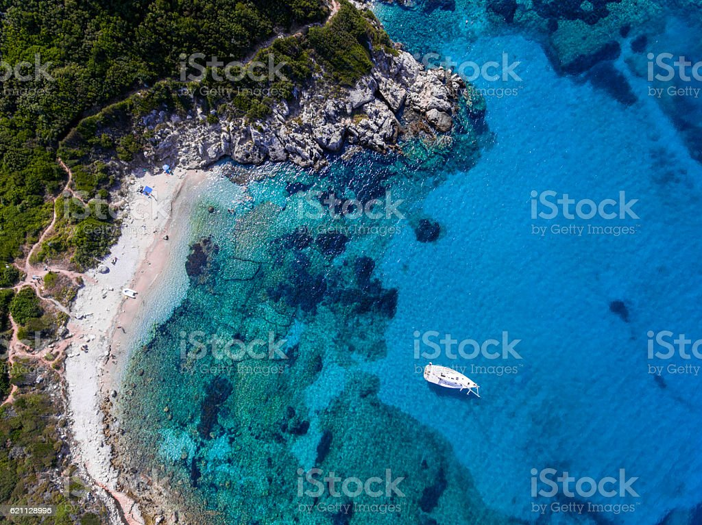 Yacht sailing in the clear blue waters of Porto Timoni, стоковое фото