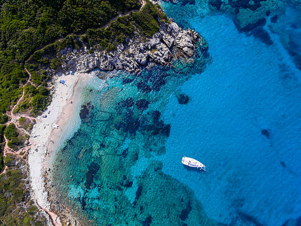 Yacht sailing in the clear blue waters of Porto Timoni, stock photo
