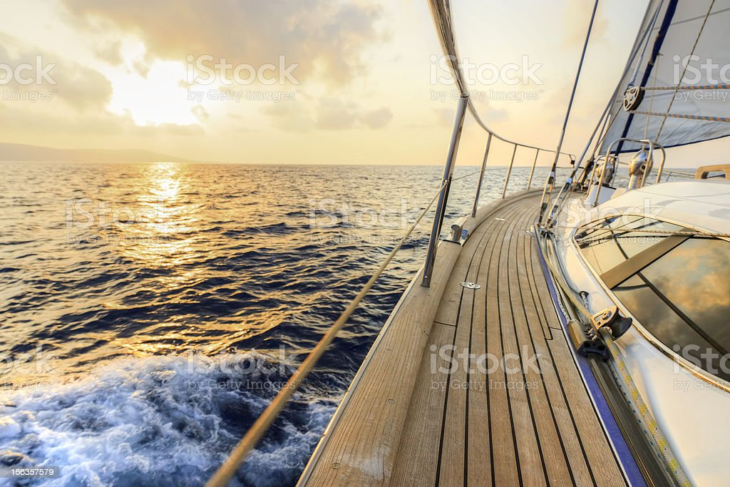 Yacht sailing towards the sunset stock photo