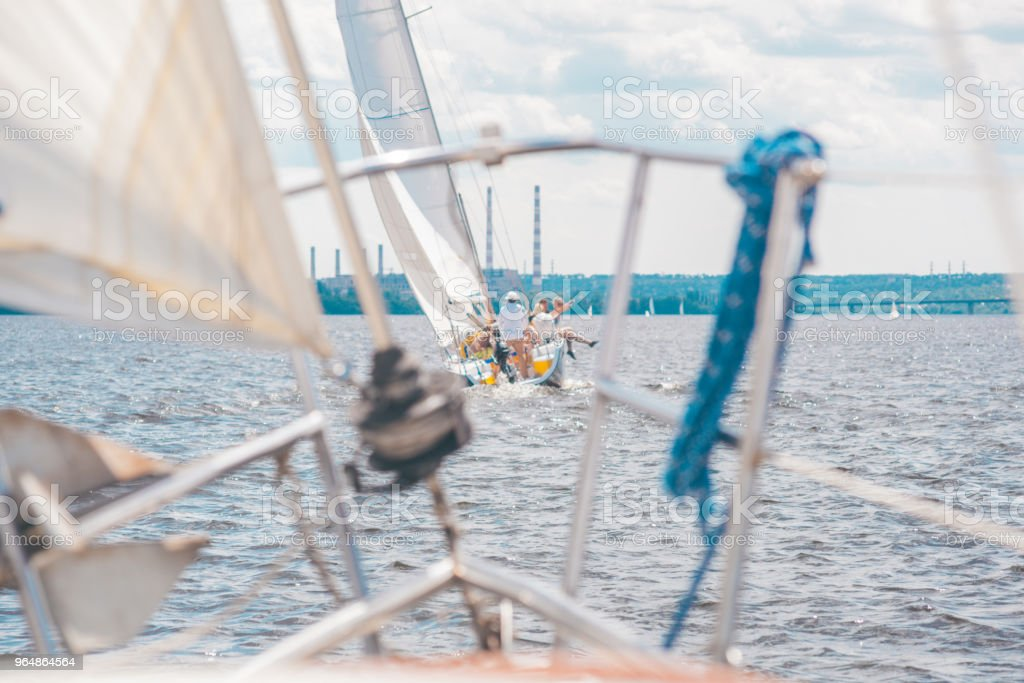 Yacht with people sails on the river on sails of white color full of wind royalty-free stock photo