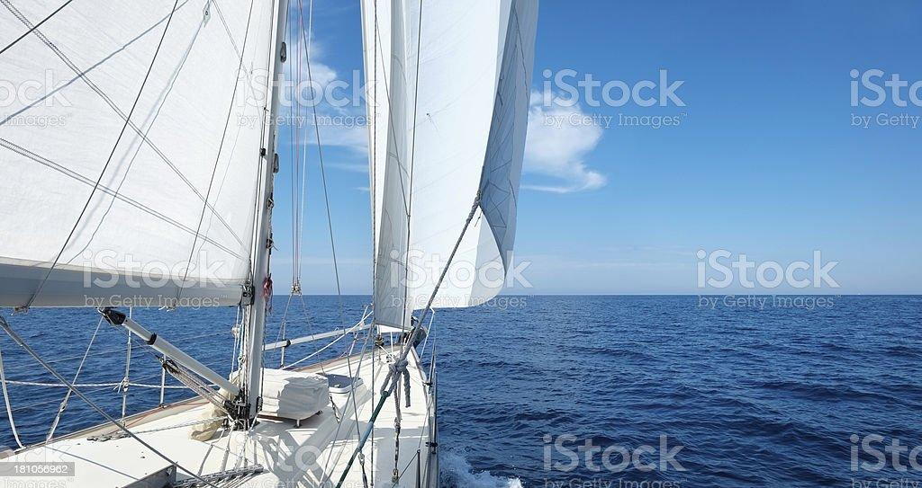 Yacht with white sails sailing towards the horizon royalty-free stock photo
