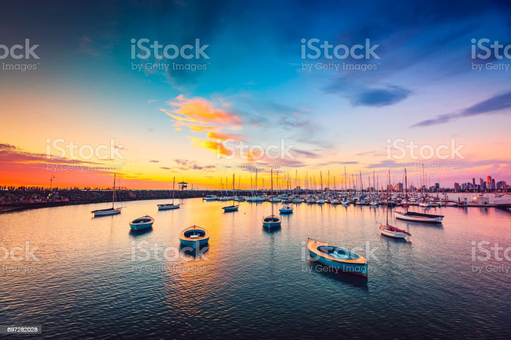 Yachts anchored in a row at sunset stock photo