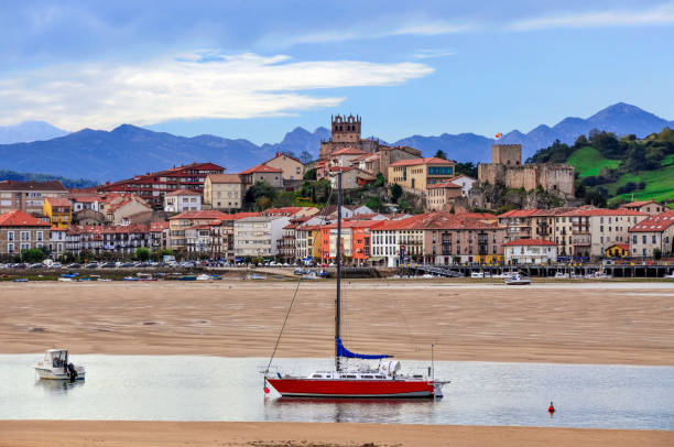 Yachts and fishing boats in the closed bay of the Cantabrian Sea against the backdrop of the mountains and the city of San Vicente de la Barquera, Cantabria, Northern Spain stock photo