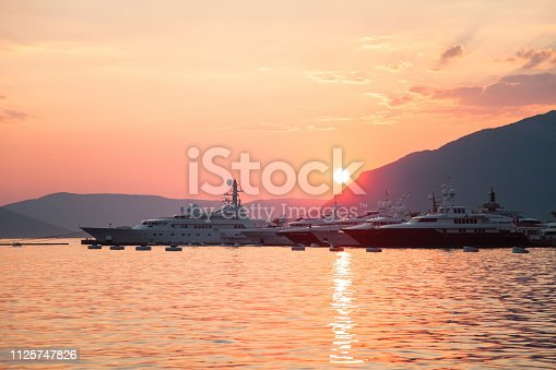 Yachts are preparing to sail in port at sunset on background of sea, mountains, sun.