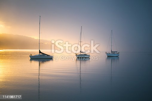 Three small sail boats or yachts on a calm mooring moored in the harbour