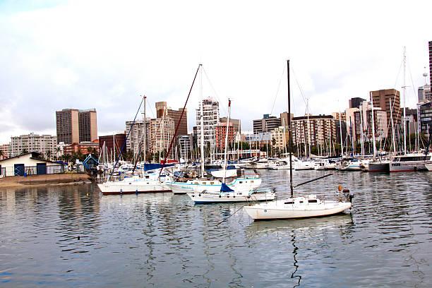 Yachten vertäut im Hafen von Durban mit Gebäuden im Hintergrund. – Foto
