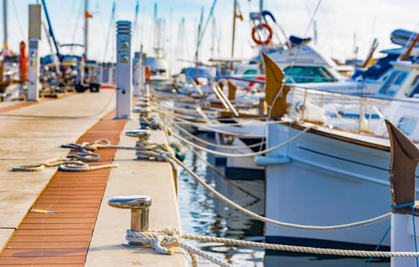 jachten aangemeerd op de haven van porto colom op het eiland mallorca, spanje - aangemeerd stockfoto's en -beelden
