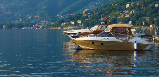 yachts moored on lake como, affected by morning light with firm water - lake como stock photos and pictures