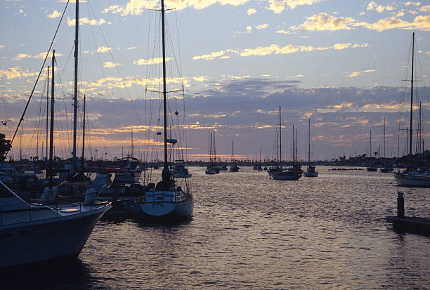 Yachts on Balboa Bay in early evening Yachts moored at Balboa Bay with dramatic clouds as the light fades into evening hearkencreative stock pictures, royalty-free photos & images