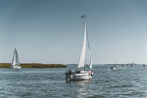 Yachts pass through the crowded Przeczka strait, which connects Mikołajskie Lake with the Śniardwy Lake in the Masurian Lake District. Masuria is a region in north-eastern Poland famous for its 2,000 lakes.