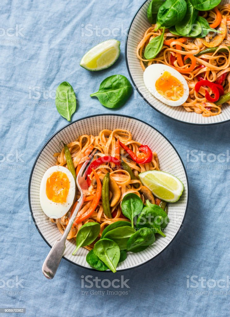 Yaki Udon noodles with stir fry vegetables, boiled egg and spinach. Vegetarian noodles with green beans, sweet peppers, mushrooms, carrots - healthy foods for lunch on a blue background, top view stock photo