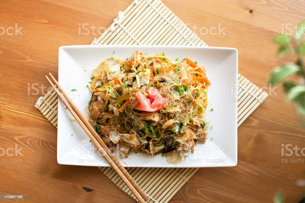 Yakisoba being served on a white plate with chop sticks stock photo