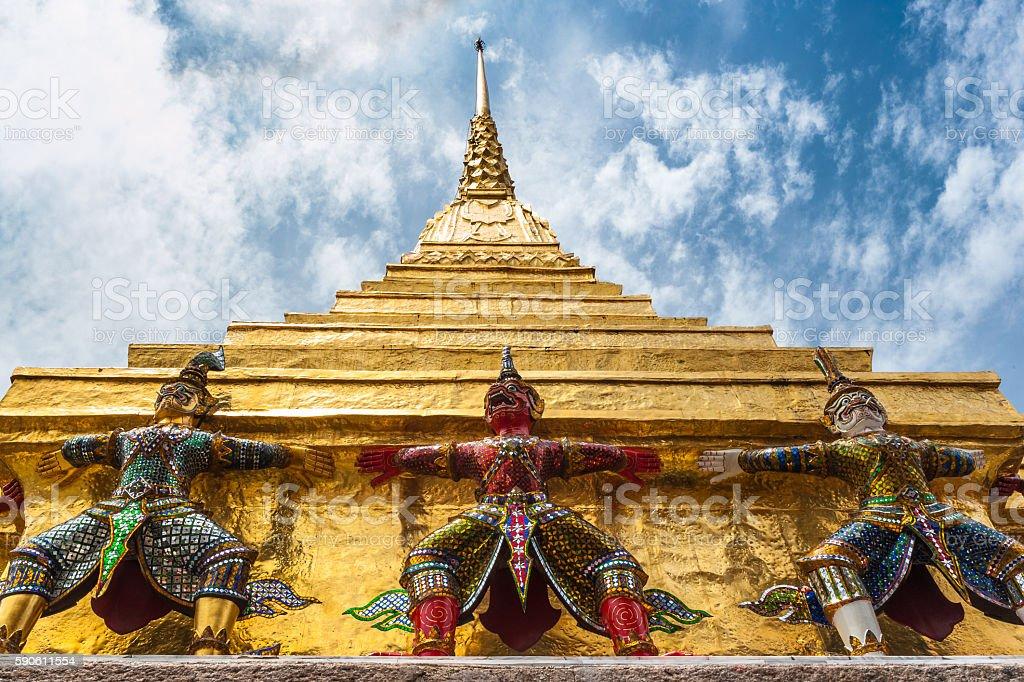 Yakshas and golden stupa, Wat Phra Kaew, Bangkok, Thailand. Low stock photo