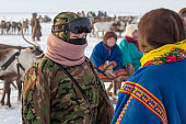 Nadym, Russia - February 23, 2020: Yamal, open area, tundra,The extreme north,  Races on reindeer sled in the Reindeer Herder's Day on Yamal, women in national clothes.