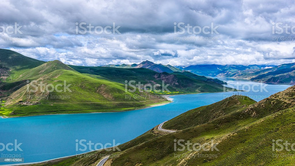 Yamzho Yumco Lake snaked across mountains in a cloudy day stock photo