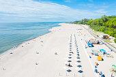 Aerial view of white wooden umbrellas and promenade on Yantarniy beach in Kaliningrad region.