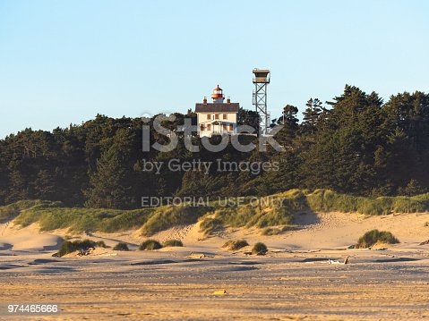 Newport, Oregon, USA - June 1, 2018: The Yaquina Bay Lighthouse is located in Newport, Oregon where it is listed in the National Register of Historic Places. Built in 1871, it was active for only a few years due to the building of Yaquina Head Lighthouse located about 3 miles north of Yaquina Bay. This view is taken from the beach looking up at the lighthouse at sunset.