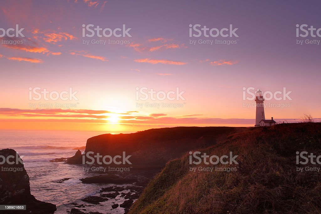 Yaquina Head Lighthouse and Pacific Ocean at sunset stock photo