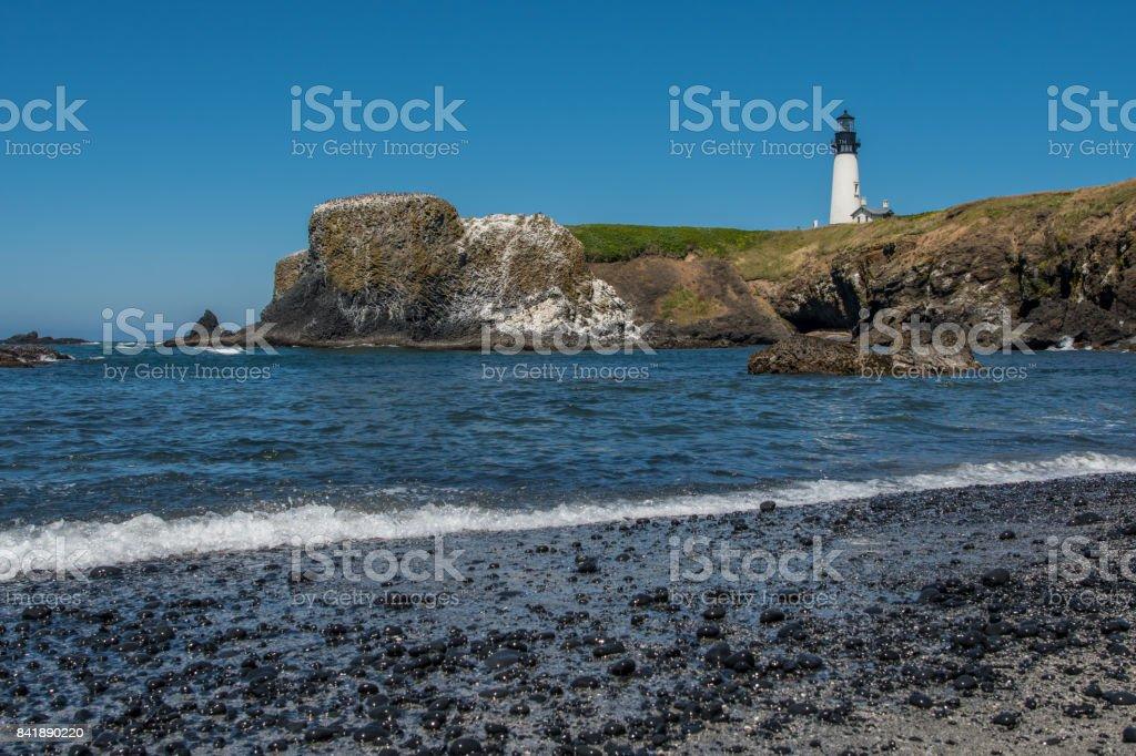 Yaquina Head Lighthouse from rocky beach stock photo